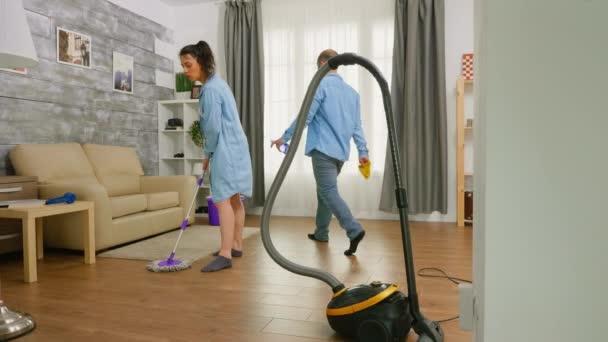 Muž utírající prach z nábytku