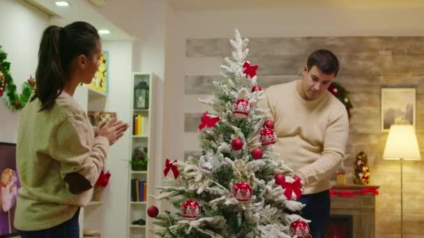 Fiatal férfi és nő díszítik a karácsonyfát