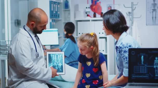 Männlicher Kinderarzt überprüft Knochen-Röntgen auf Tablet