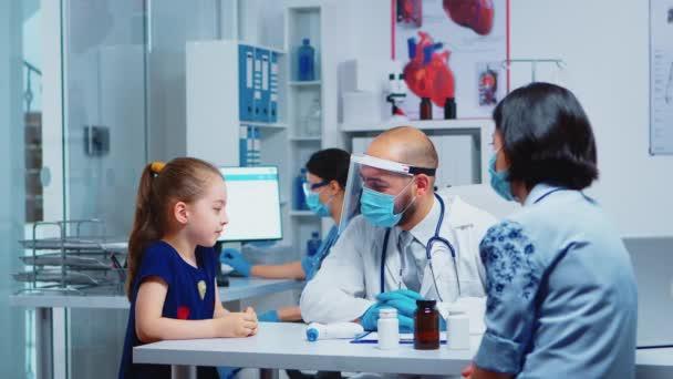Kleines Mädchen spricht während der Konsultation mit Arzt