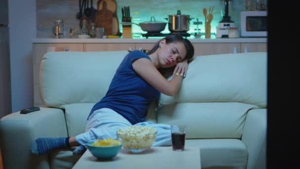 Žena spí na gauči před televizí