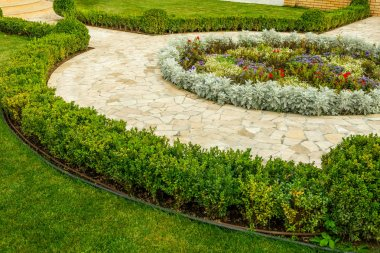mowed lawns with shrubs near the stone walkway