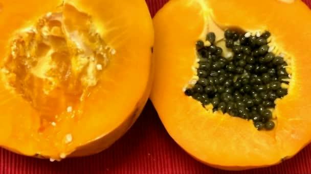 Papaya - eine tropische Frucht in Form einer länglichen Melone, mit essbarem orangefarbenen Fruchtfleisch und kleinen schwarzen Samen auf roter Stoffserviette.
