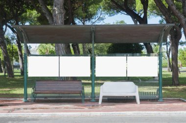 Empty bus stop with blank advertising spaces near to a park