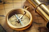 Fotografie antique compass, spyglass on map
