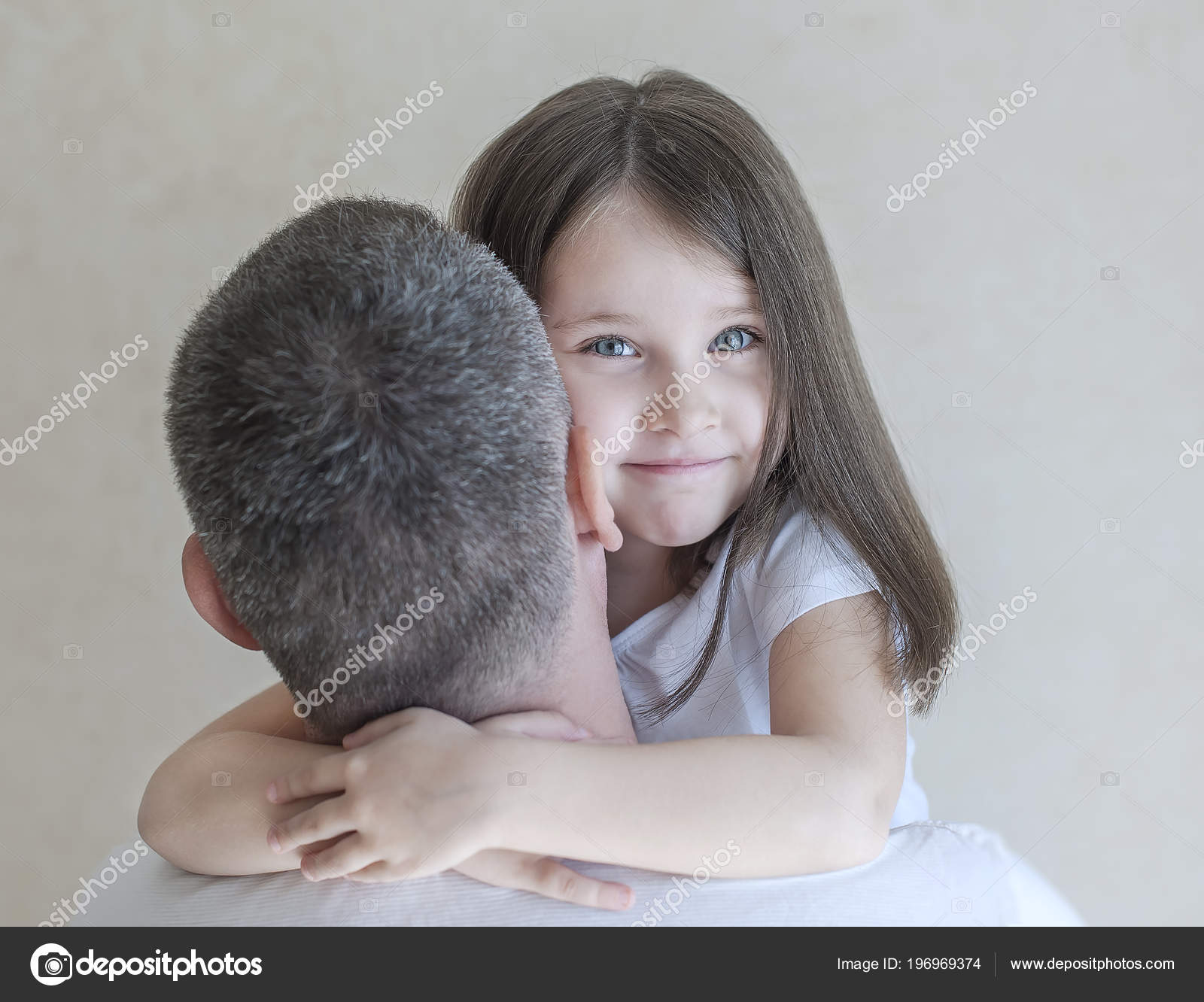 8195f219 Portrait of cute little girl held in father's arms. Happy loving family.  Father and his daughter child girl playing hugging. Cute baby and daddy.