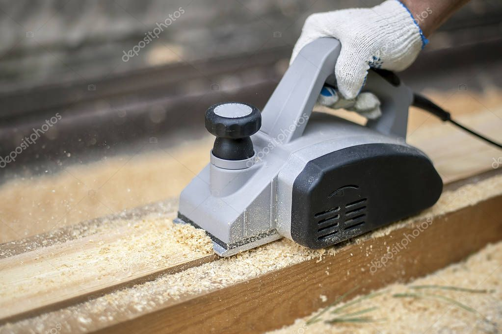 Man planing boards with electric tools, chips flying in all directions. Construction, wood processing