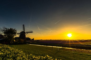 sunset sky and wooden windmill on meadow