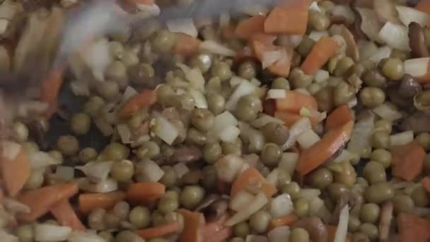 Karotten mit Zwiebeln, Pilzen und Erbsen zum Braten in der Pfanne