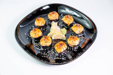 photo of baked Japanese rolls in a black plate