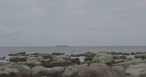 stony Baltic sea shore cargo ship floats on the horizon in cloudy autumn weather