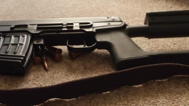 Waffen und Munition aus nächster Nähe auf dem Teppich. reibungslose Kamerafahrt