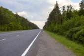 Strada nellitinerario di campo, a lunga distanza nel campo. Colline verdi. Cielo blu con le nubi lanuginose. La strada che va oltre lorizzonte