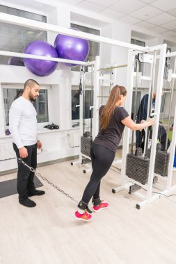 Woman exercising legs with personal trainer at gym using cable crossover machine