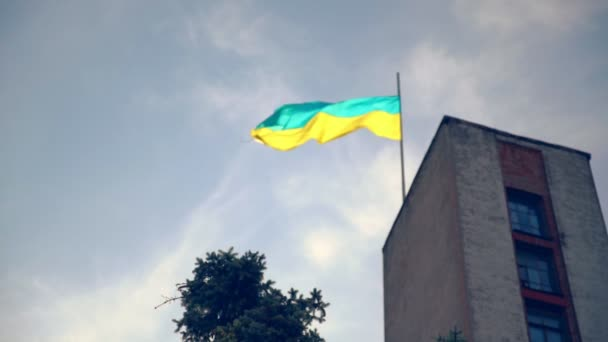Ukrajinská vlajka vlaje na sloupu na budovy