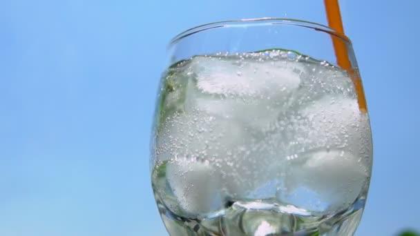 Za stálého míchání sklenici čerstvé ledové vody se slámou