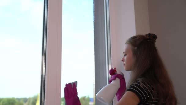 Mladá žena nosí rukavice čištění okna