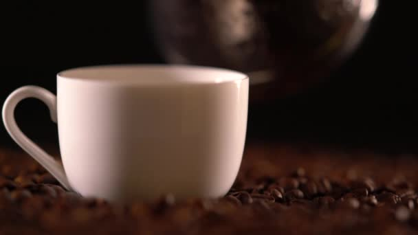 Person pouring brown liquid into small cup