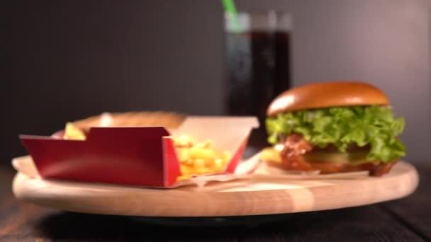 S sebou hamburgery, smažené bramborové hranolky a soda