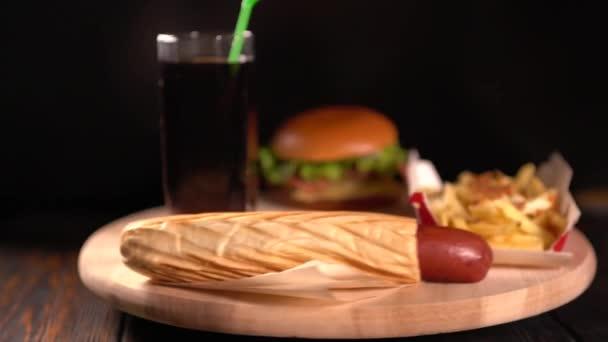 Rotující grilovaný párek v rohlíku, hamburger, hranolky a soda