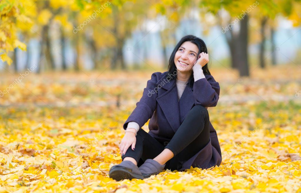 Happy young woman sitting daydreaming in a park sitting on the ground amongst colorful autumn leaves smiling to herself