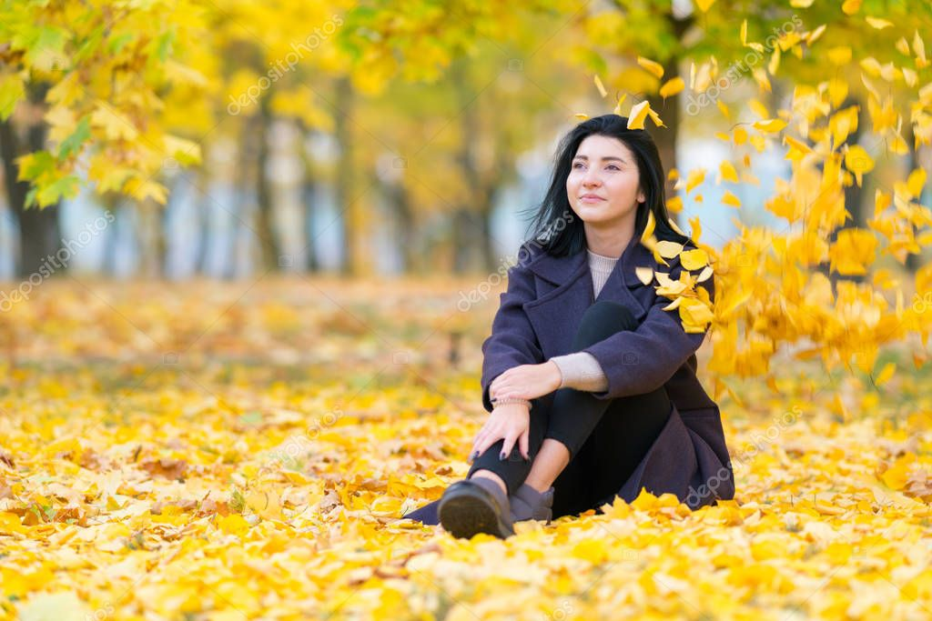 Young woman sitting in an autumn park amongst colorful yellow leaves smiling as she daydreams