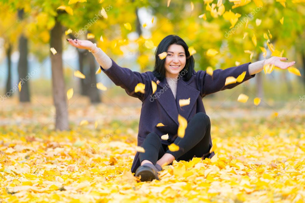 Happy young woman throwing autumn leaves in the air as she sits on the ground in a wooded park smiling at the camera
