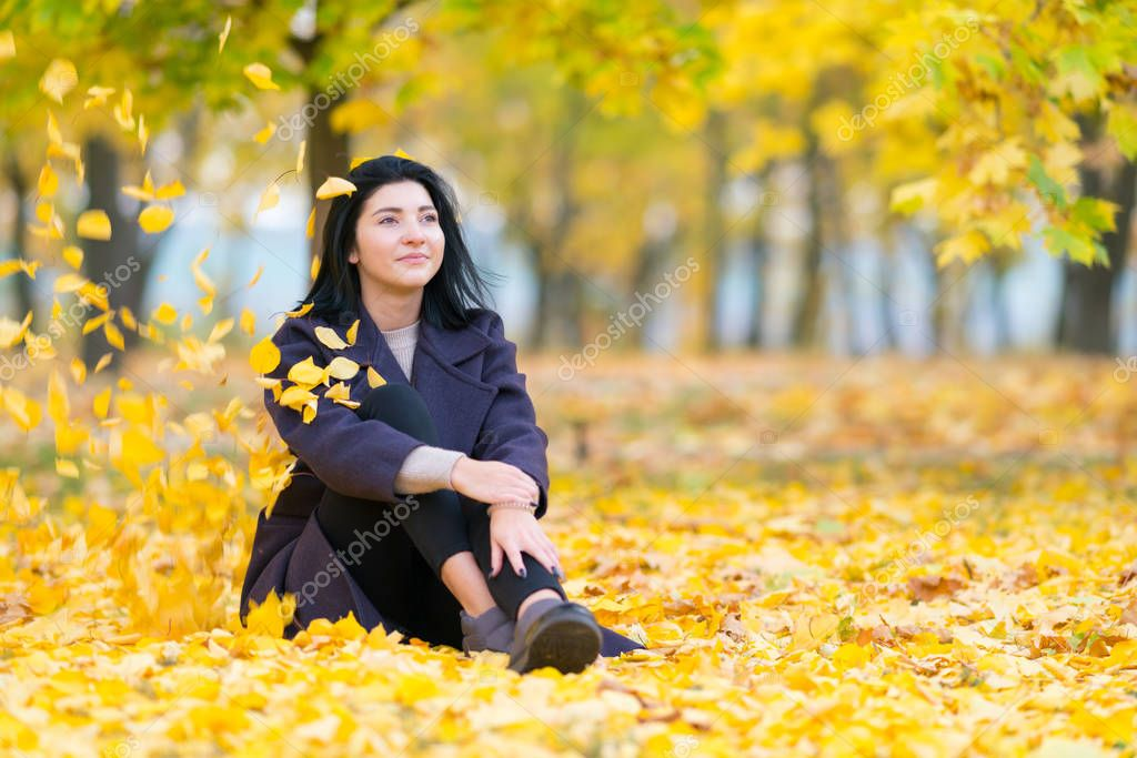 Woman sitting daydreaming amongst colorful yellow leaves in a park in autumn staring up with a quiet smile of pleasure