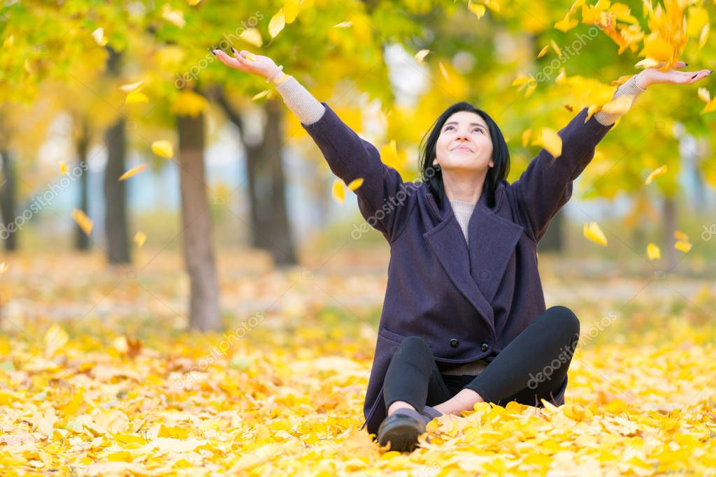 Carefree young woman celebrating the autumn season tossing colorful yellow leaves in the air as she sits on the ground in a park