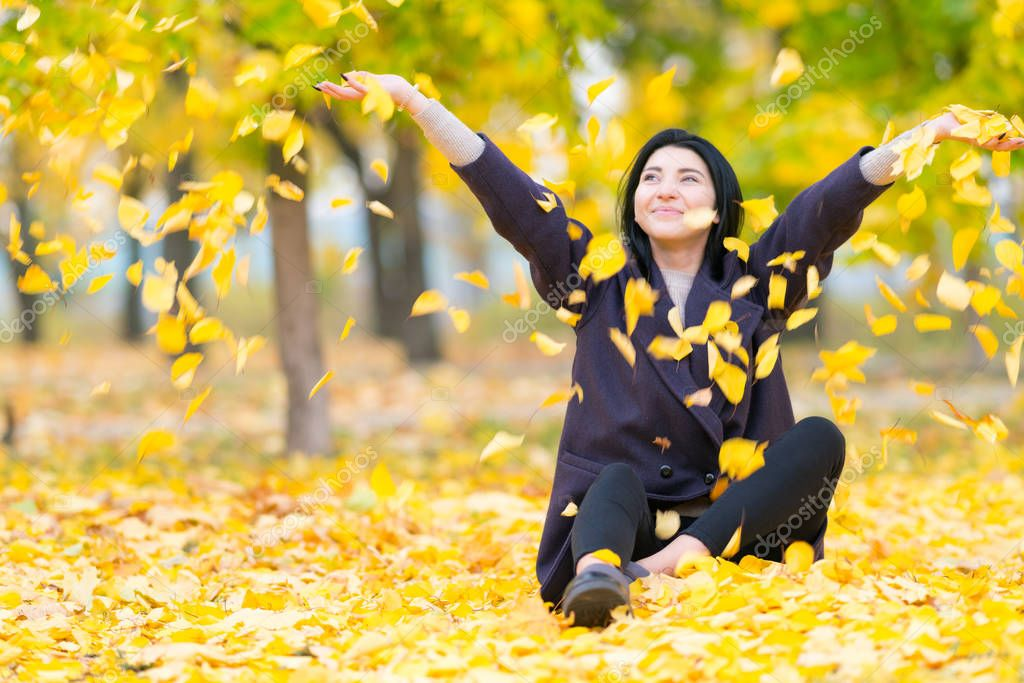 Happy young woman throwing yellow autumn leaves into the air as she sits on the ground in a park