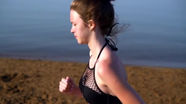 Attractive fit young woman jogging on a beach