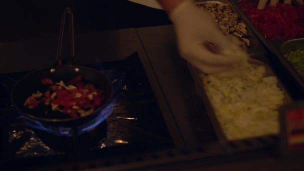 Koch wählt frische Zutaten in einer Pfanne aus