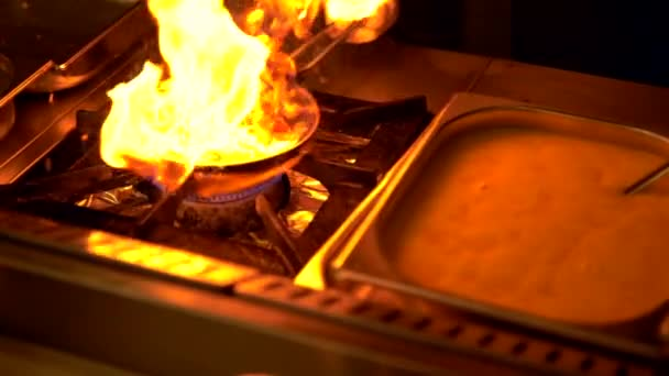 Šéfkuchař planoucí čerstvé ingredience na omeletu