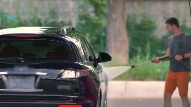 Man washing a car using a high pressure system
