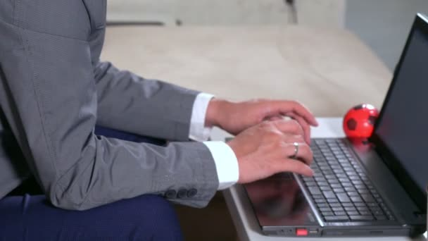 Businessman typing on a laptop keyboard