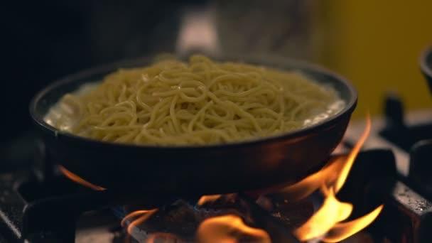 Těstoviny doutnající v omáčce nad horkým ohněm
