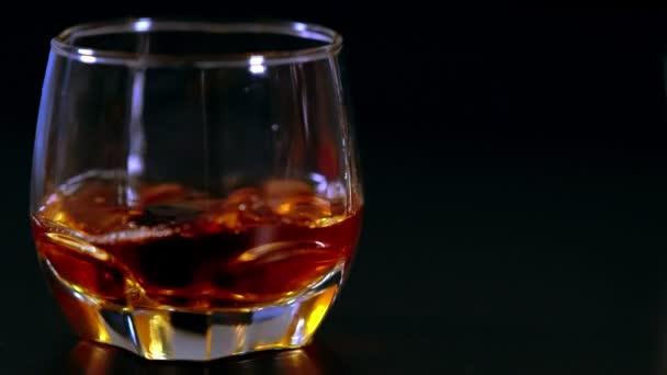 Jégkockát dobni egy pohár whiskybe.