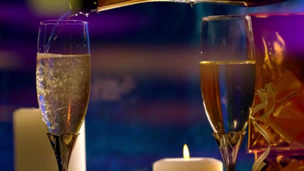 Pouring two flutes of champagne by candlelight