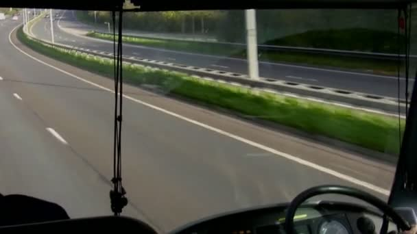 Windshield and dashboard view from inside of bus or coach driving on a highway in England, United Kingdom