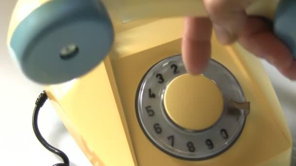 Detailní záběr Staré věku rotační pevná linka telefon na bílém pozadí. Ruční vyzvedávání přijímač nebo sluchátko a vytáčení Evropské tísňové telefonní číslo 999 čeká policie, sanitka a oheň, Velká Británie, Velká Británie, Evropa a Commonwealth zemích