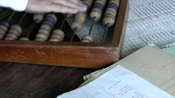 Retro scéna uvnitř znázorňující účetní počítat náklady nebo zisk pomocí abacus na dřevěný stůl s papíry