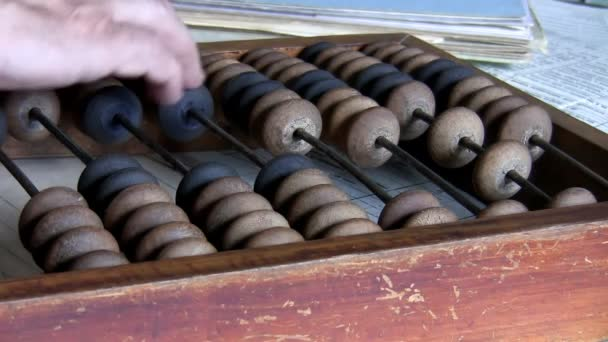 Close up of hand of man counting finance using old style calculator, wooden abacus