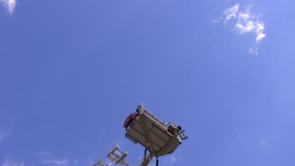 Teleskopické hasiči žebříkem nebo platforma se zvyšuje s lidmi v něm. Modrá obloha pozadí
