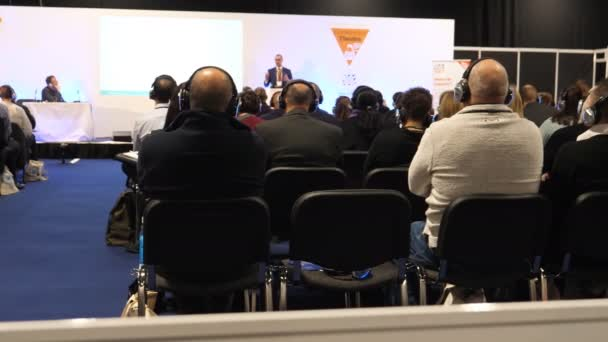 Manchester, ENGLAND, UNITED KINGDOM - SEPTEMBER, 2018: People sitting in black walled Event City venue, the space arranged for conference and listening through wireless headphones to lecturer speaking in front of audience
