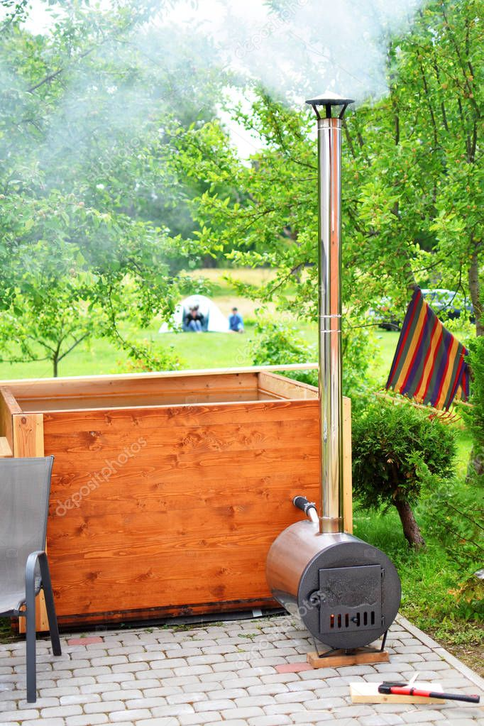Wooden hot tub with smoky chimney and furnace outdoors in yard on apple tree garden and blurred tent with people background in summer.