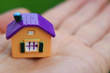 Hand holding little colorful house closeup view with copy space for text. Real estate, buying and moving new home concept.