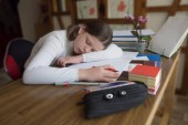 Teenager girl sleeping tired at the table during homework with a pen in hand, on the table there are a pencil case with pens, stand for books, notebooks, a stack of schoolbooks and an orchid in a pot