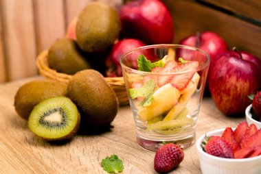 Fruit salad cooking with apple wiki stawberry in glass on wood background