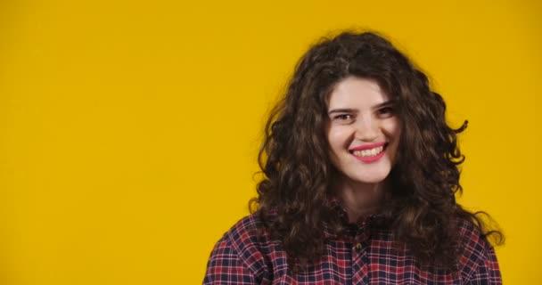 Detailní záběr atraktivní plus-size model pózování. Kudrnatá bruneta na jasně žlutém pozadí předvádějící různé emoce. Dívka flirtuje, usmívá se a narovnává si vlasy.