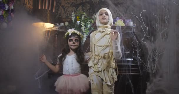 Dvě dívky oblečené v halloweenské mumii a kostýmech Santa Muerte tančících ve starém tmavém gotickém interiéru pokrytém pavučinami a tajemnou mlhou. 4K zpomalení 50 fps